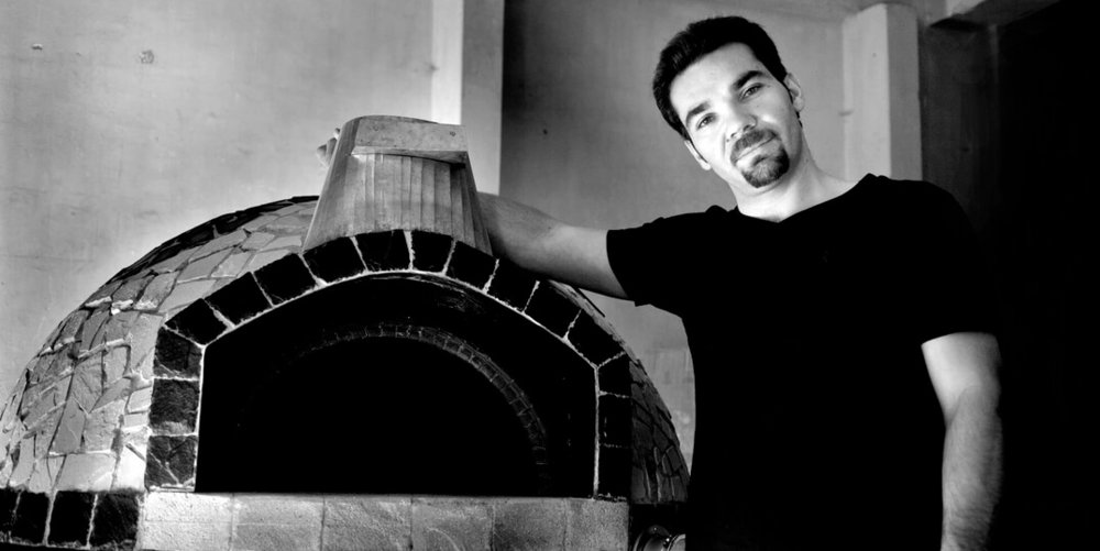 "Italian Marco Cappiotti, also known as ""Il Forno By Marco"", in front of his semi-mobile wood fired pizza oven."