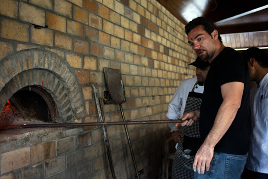 Marco cooking a pizza in his fixed wood fired oven.
