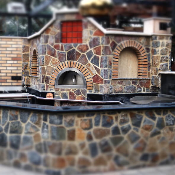 Fixed brick oven with stone finishing. In front of the oven there is a stone wall.