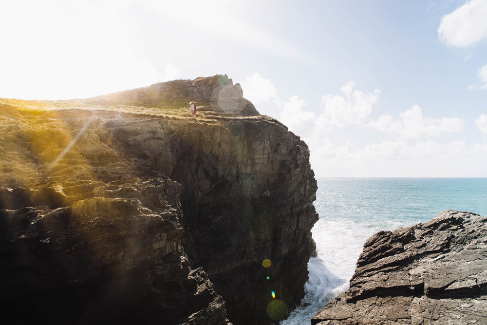 Couple on the edge of the cliffs in Newquay for Beach Retreats | Karl Mackie Photography