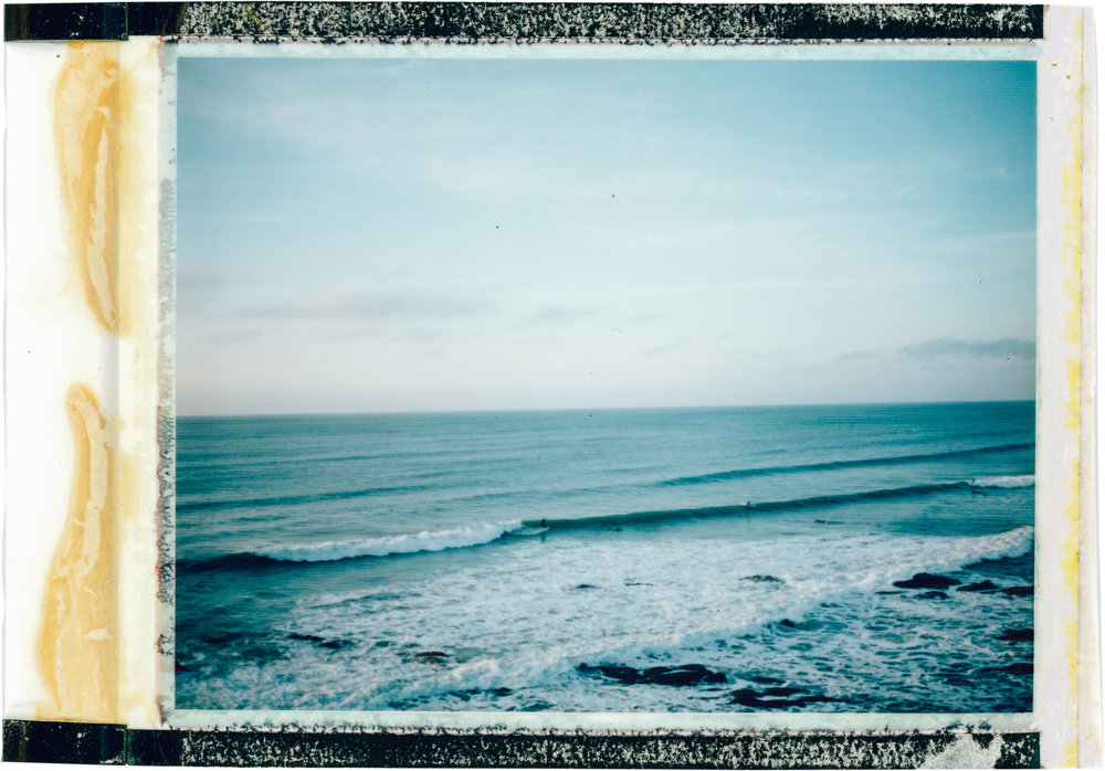 Surfers on Polaroid out at Fistral Beach | Karl Mackie Photography