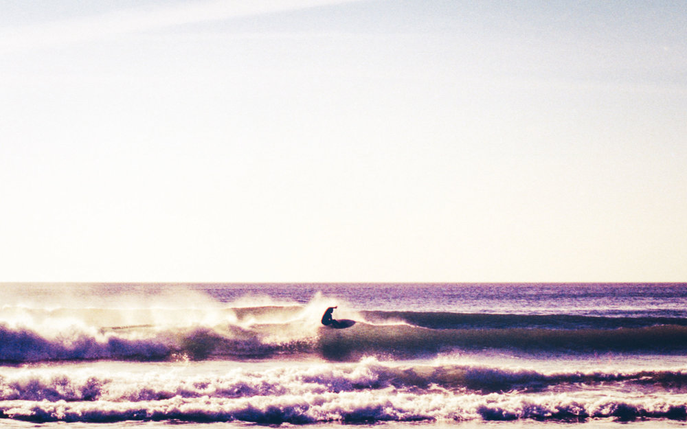 Surfer getting air at Fistral Beach | Karl Mackie Photography