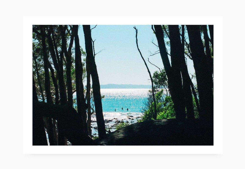 Surfers between the trees at Tee Tree Bay | Karl Mackie Photography | Art Print