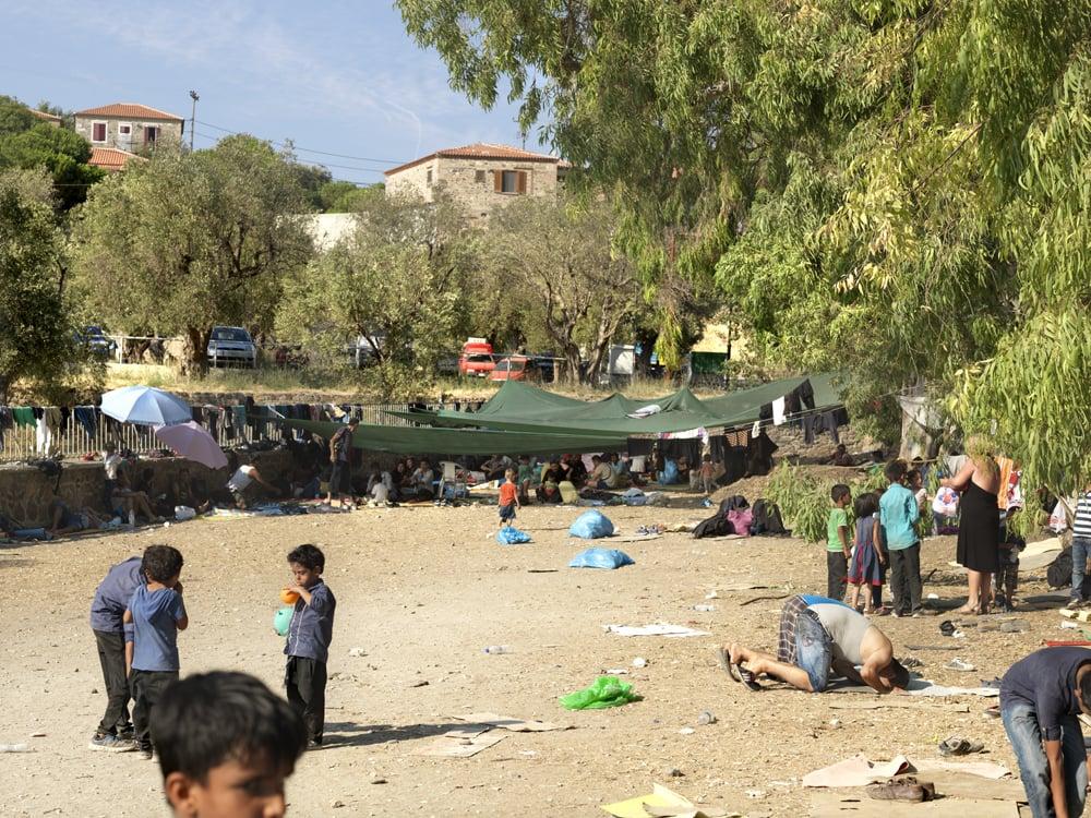 De parkeerplaats van Molyvos waar vluchtelingen verplicht moesten wachten op een bus die hen naar Mythilini bracht. Het was er 35 graden en er was amper schaduw.