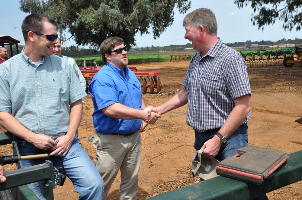 Lee Fairchild presents Schoeman Boerdery (farms) CEO Brett Parrott with an LSU AgCenter Cap as Tripp Shepherd looks on.