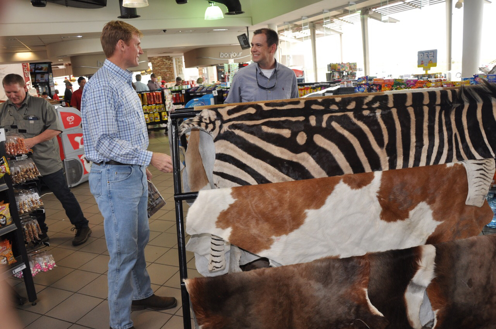Chip Hixon, Patrick Frischhertz, and Tripp Shepherd examine the quality of hides on sale at a convenience store near Belfast, South Africa.