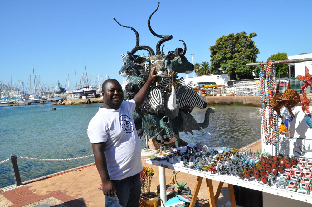 A vendor, named Innocent, shows off his hand-made crafts in the Simon's Town Harbor.