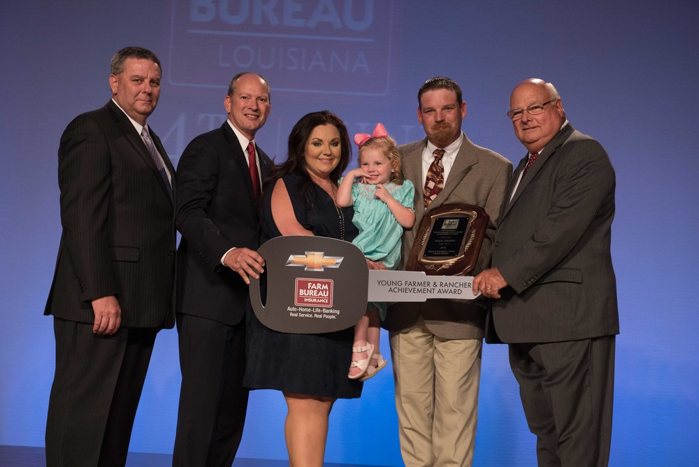 Ryan & Danielle Yerby of Grant Parish are Louisiana's top young farmers for 2016, taking home a $40,000 credit towards a Chevrolet or GMC truck, courtesy of the Southern Farm Bureau Casualty Insurance Company.  Pictured L to R:  Duff Wallace, Southern Farm Bureau Casualty Insurance Company, Blaine Briggs, Louisiana Farm Bureau Mutual Insurance Company, Danielle Yerby, Reagan Yerby, Ryan Yerby, Ronnie Anderson, Louisiana Farm Bureau President