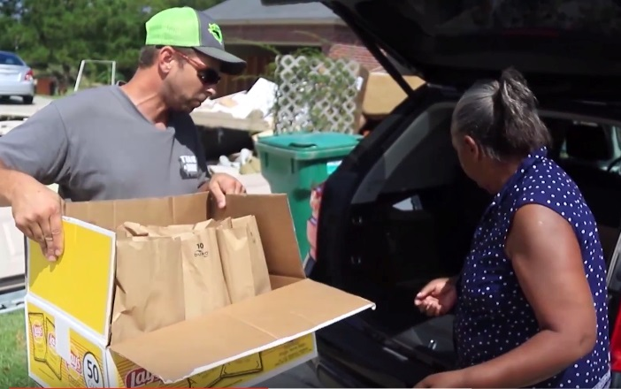 Billy Doiron, a cattle rancher in Livingston Parish, passes out food and supplies to one of the many flood victims in his area.  More than 90 percent of the homes in his parish were affected by the flooding last month.  Doiron said it wasn't enough to just take care of his operation, he had to help neighbors get back on their feet in any way he could.