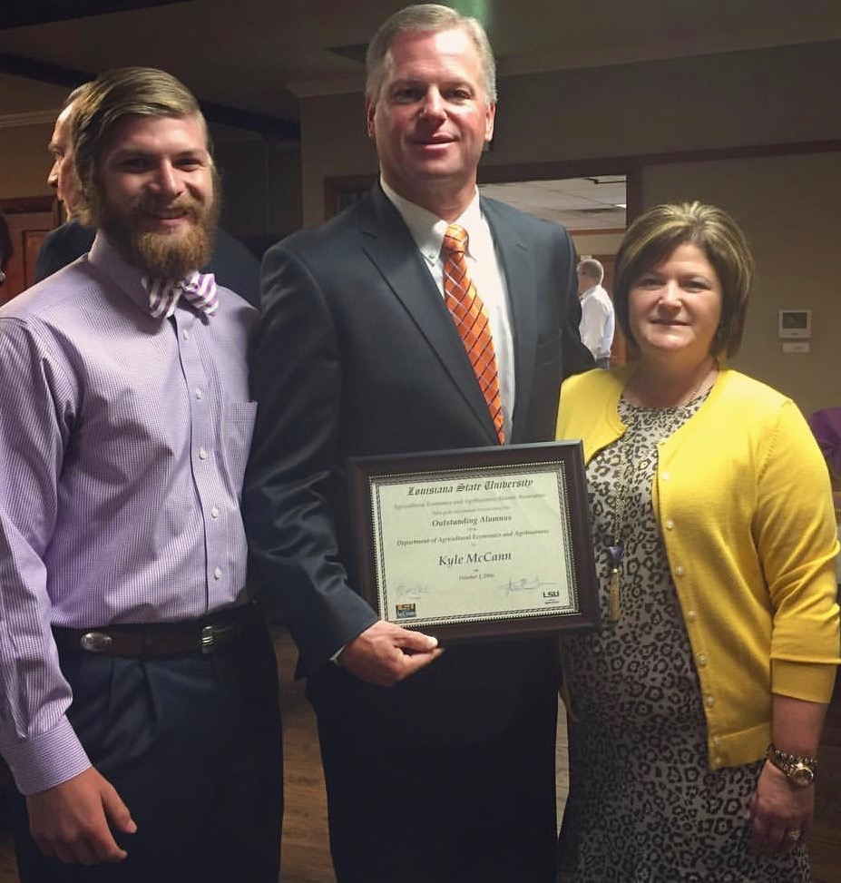 Kyle McCann, center, associate commodity director for the Louisiana Farm Bureau, was named as the 2016 Outstanding Alumnus recipient at the annual LSU Ag Economics and Agribusiness Alumni Recognition Ceremony. He is pictured here with his wife Daphane, right, and his son James, left.