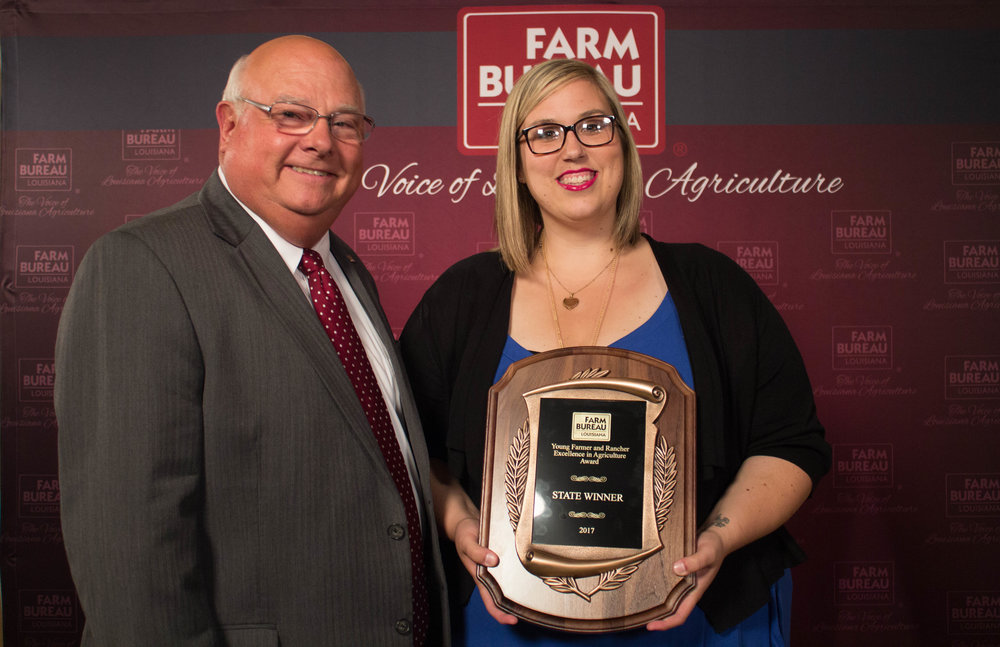 Louisiana Farm Bureau President Ronnie Anderson presents the 2017 Excellence in Agriculture Award plaque to Katie Sistrunk of Iberville parish.