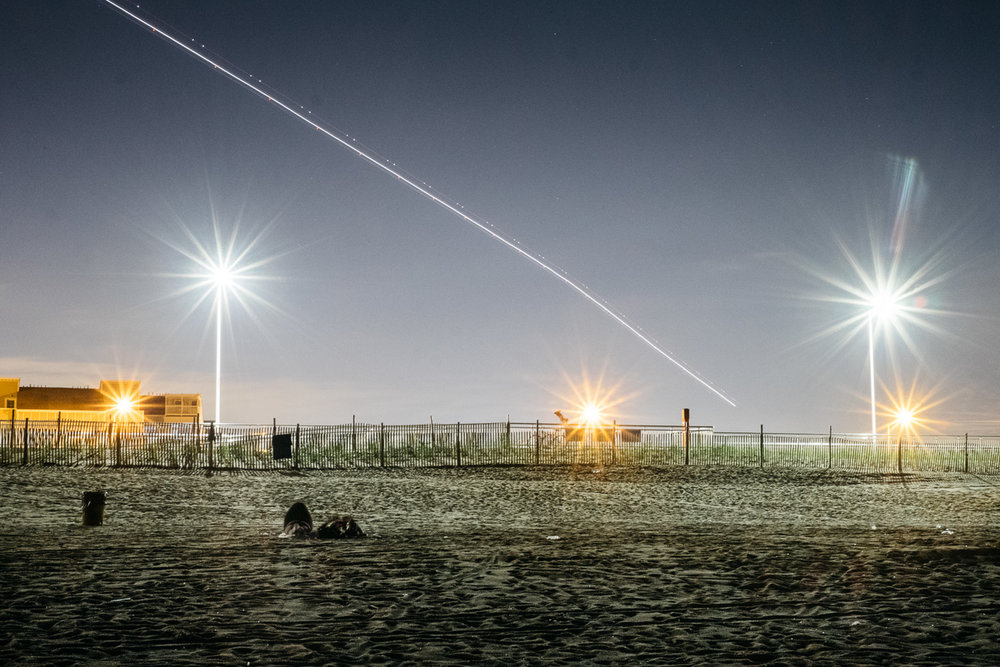 Couple on beach at night, with plane flying overhead. Rockaway, Queens, NYC 2016