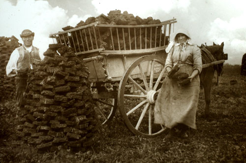 An Irish couple loads turf into their cart (c, 1905)