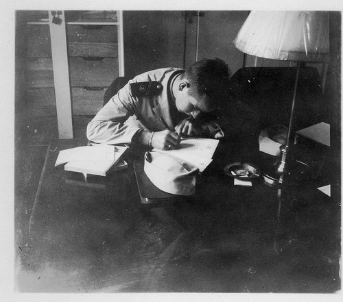 Man writing at desk vintage photo (in public domain). Authenticity through writing.