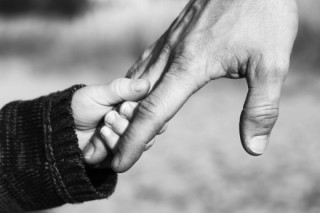 Father holding child's hand image.