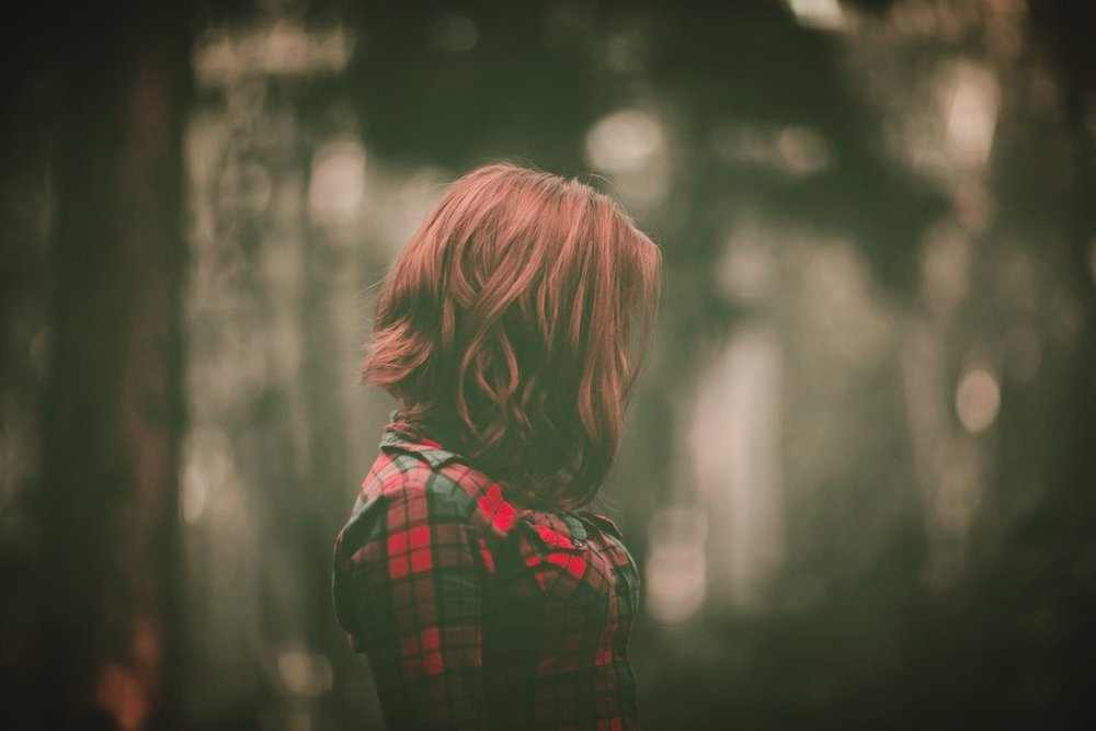 Red-haired woman standing in forest. (cco Image)