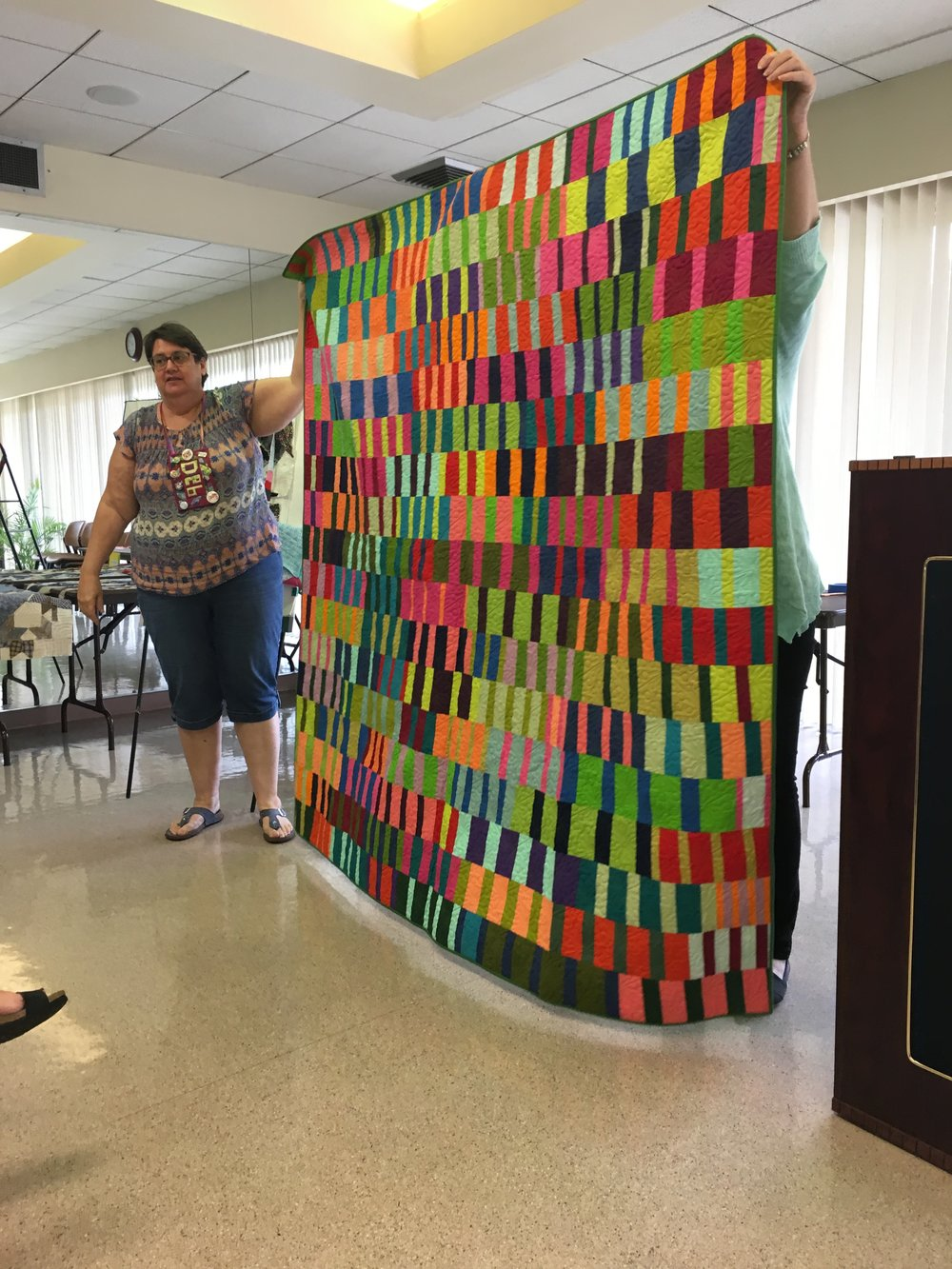 Debbie with her finished quilt. Started in a Tara Faughnan class at QuiltCon 2017.