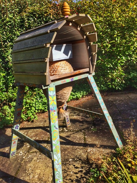 A sun hive with a rain protection cover and a box for surplus honey stores on top.