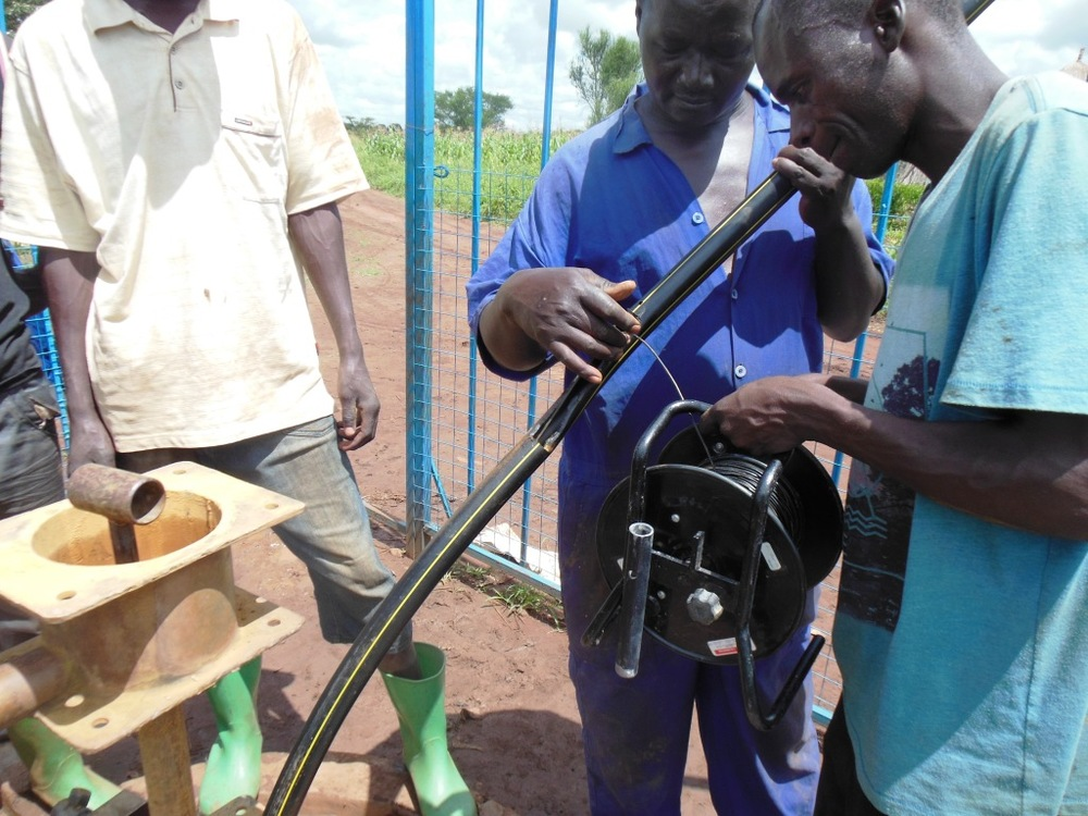 East Well insert is the first Solinst transducer being inserted into the well on the Family Empowerment Farm near Masindi, UG.