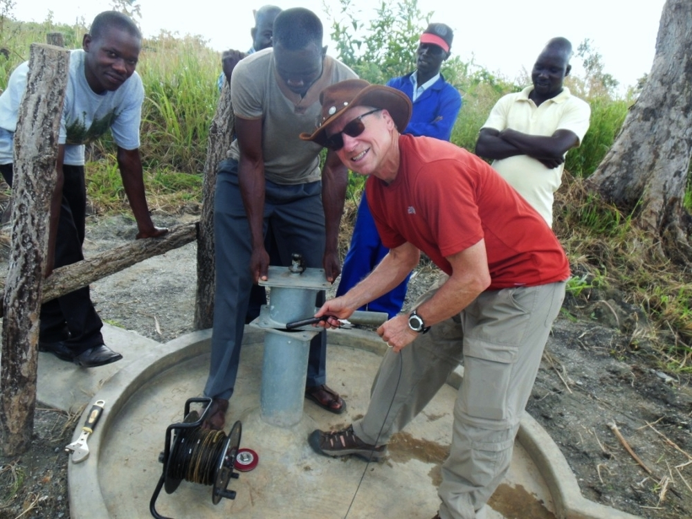 Deploying the Solinst Levelogger transducer into the Opit goat property water well.