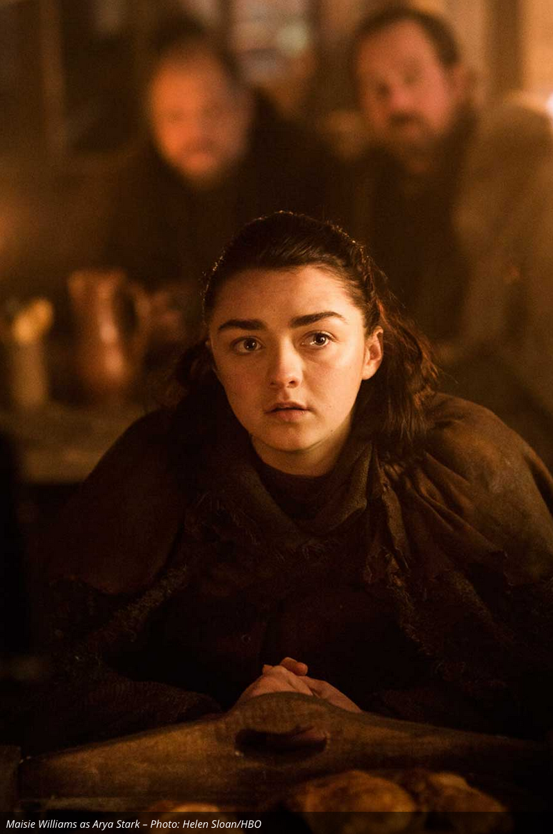 Arya is in an inn or tavern listening to someone intently. We don't know her specific location, but my best guess is that she is still traveling around mid-Westeros plotting her next move.
