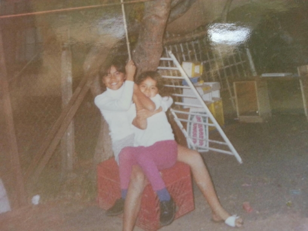 Me, with my younger sister Grace, swinging on a swing made from a milk crate and rope.