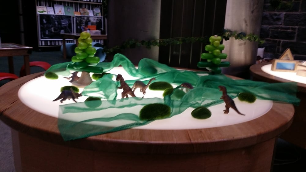 Dinosaurs, mossy rocks and assorted greenery create a 'wild' light table for 'Where the Wild Things Are' in Play Pod, State Library Victoria.