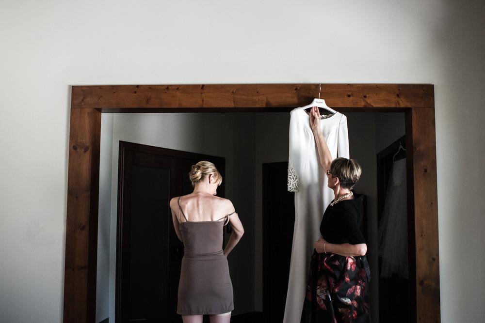 066-mother-helping-bride-put-dress-wedding-photographer-toronto.jpg