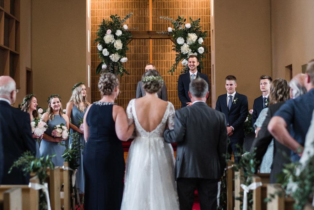 192-groom-reaction-seeing-bride-down-aisle-wedding-ceremony-wooden-arch.jpg