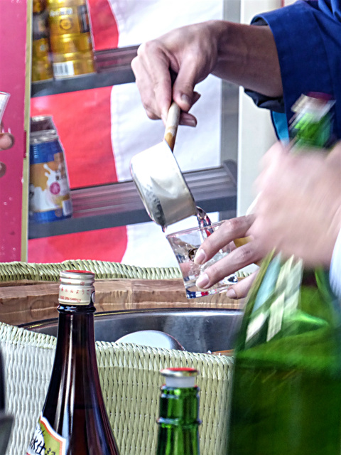 Fresh brew of sake being served one after another by a ladle at 'Kurabiraki' open day