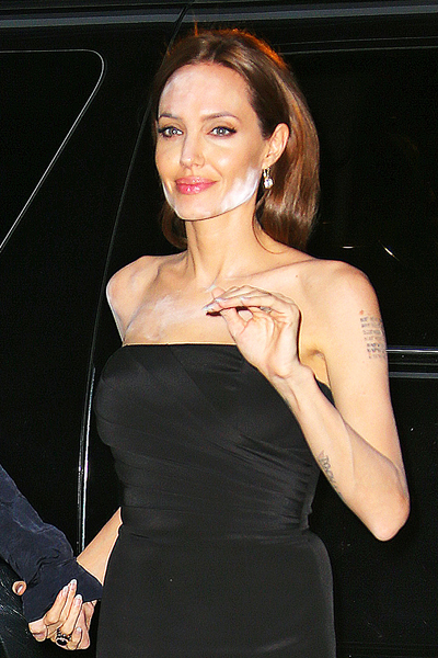 Angelina Jolie suffers a major makeup-malfunction where the make up on her face appears to be paste-y or powdery and doesn't match her skin tone
