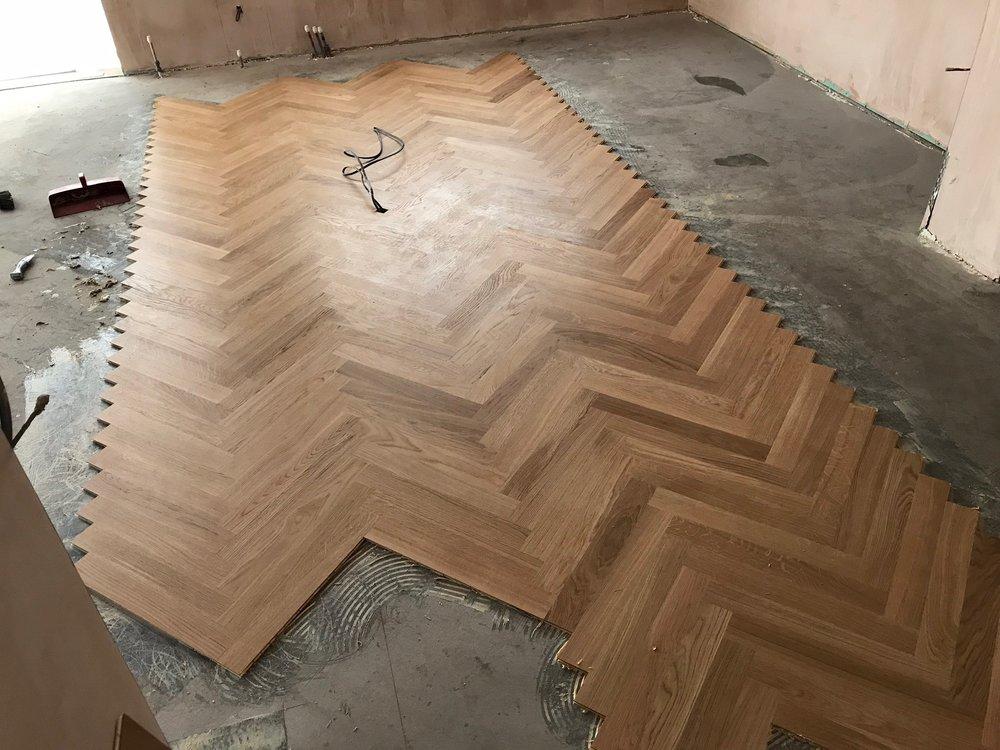 Floor goes down: Oak veneer herringbone parquet.
