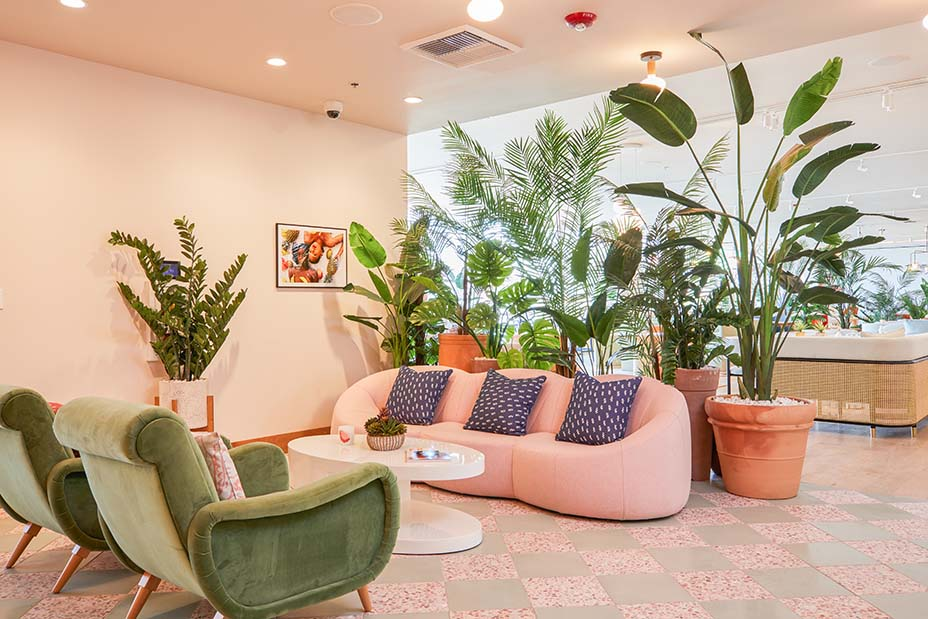 "The entrance of The Wing with a 1st Dibs table and a pink Pierre Poulin ""pumpkin sofa,"" inspired by a Palm Springs vibe. Image Madeline Tolle/The Wing."