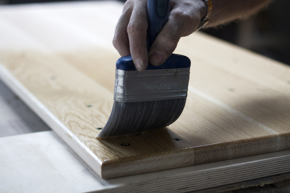 Carefully applying a surface finish to an oak table