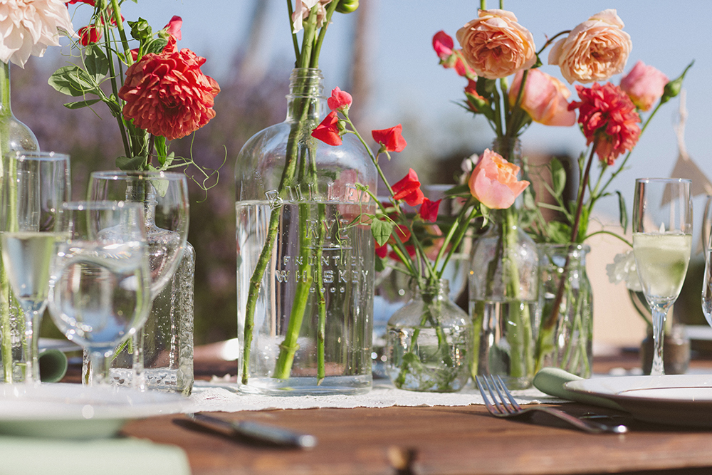 We wanted casual centerpieces that were inexpensive and had a wild look. We collected dozens of different bottles and jars (check your local bar/restaurant!) and filled them with small collections of bulk flowers in our wedding colors--coral, peach, and succulent greens. Flowers: Gorgeous & Green Photo: Kristian Melom