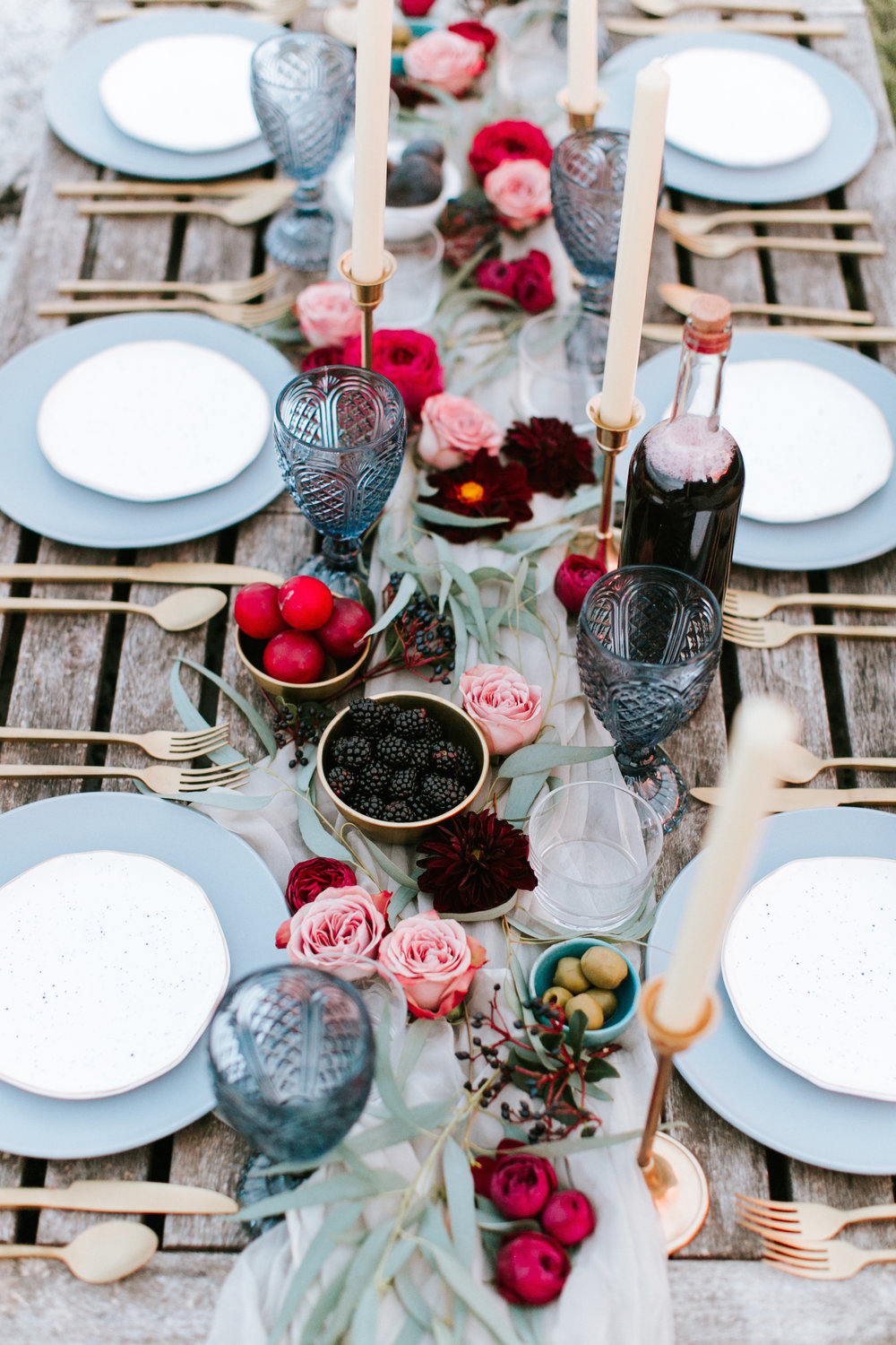 Get the look: Gold candleholder, matte gold cutlery, sapphire goblets
