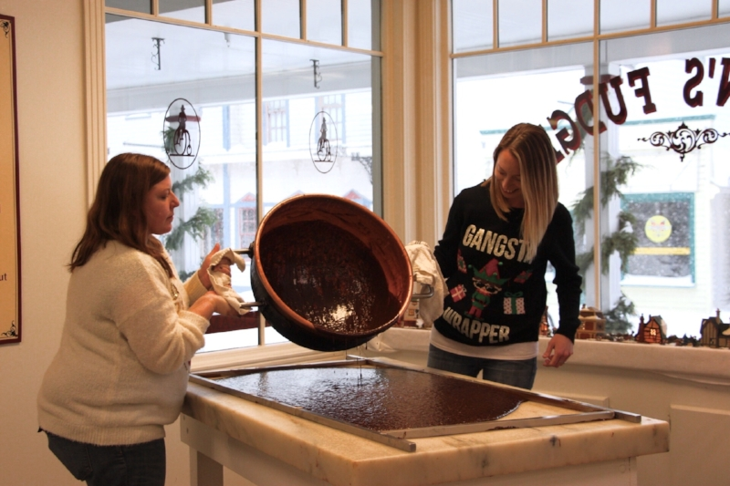 Pouring the fudge from the copper kettle to the marble table