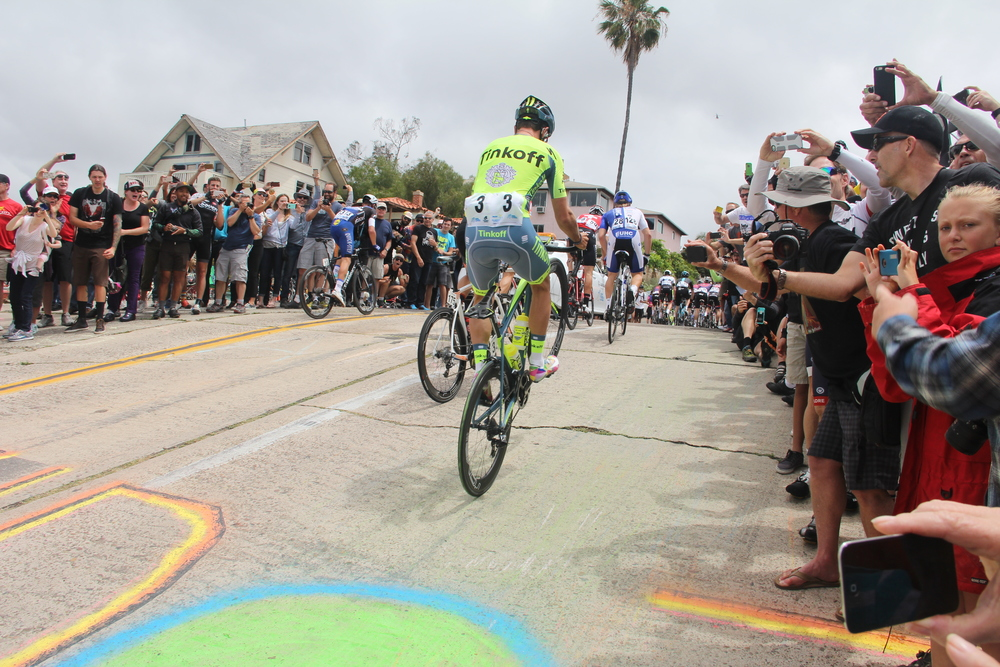 Adam Blythe of the Tinkov team pops a wheelie for the crowd while climbing up Laurel Street.