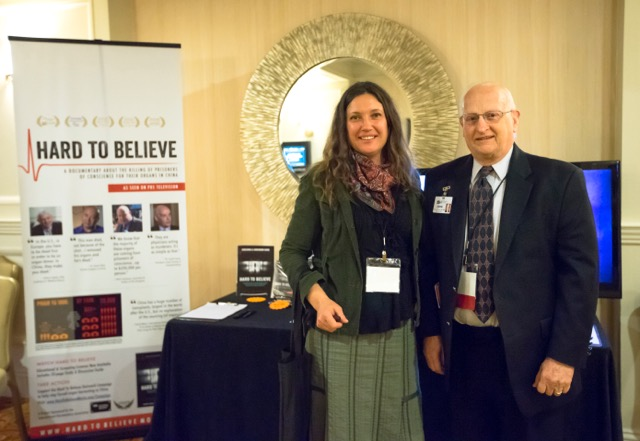 "Swoop Films representative, Yulia Felton (L) and Dr. John Graham, President and CEO of the Institute of for Spirituality and Health (R) at the ""Hard To Believe"" exhibit."