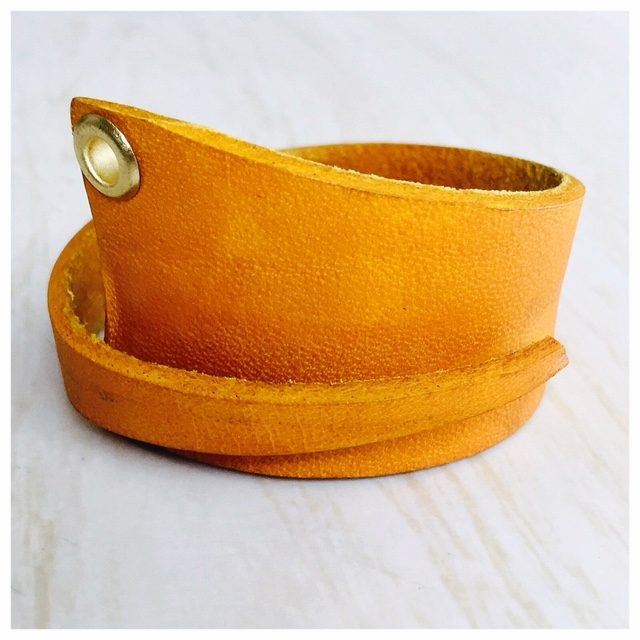 Adjustable, yellow-dyed leather bracelet with eyelet detail.