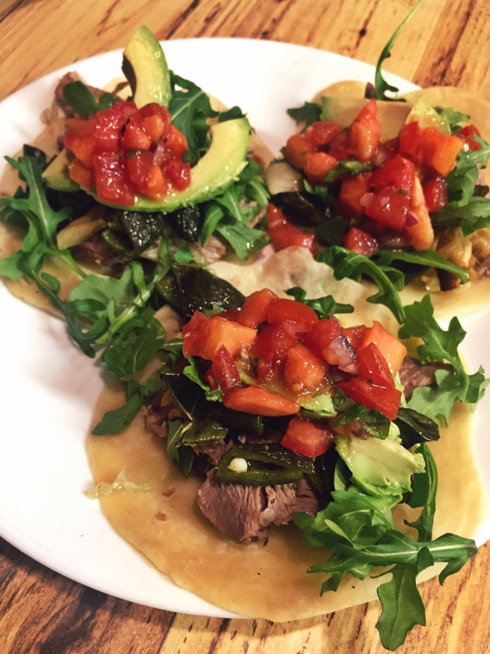 Pork tacos with roasted poblano peppers, arugula, avocado, and fresh papaya salsa with handmade flour tortillas.