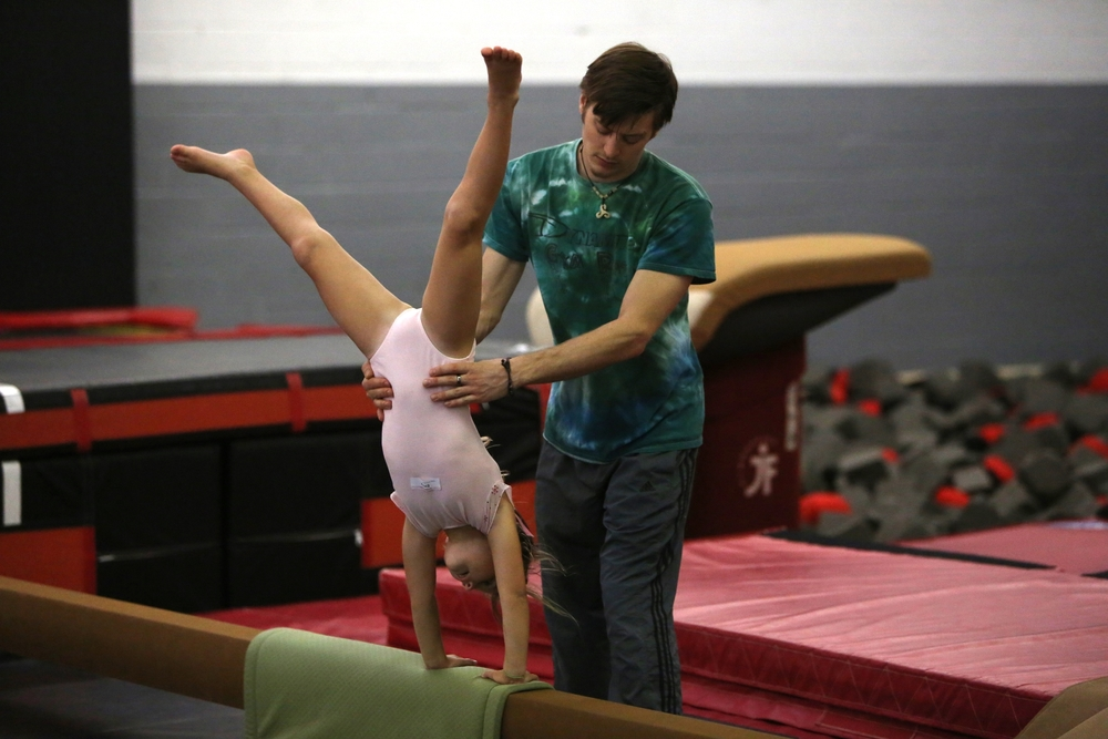 Mr. Patrick helping Snaps on cartwheels on beam