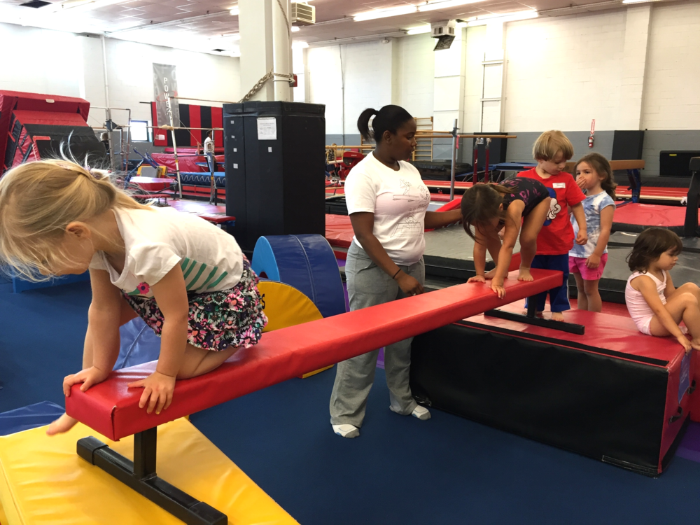 Ms. Tosha helping Firecrackers across a beam