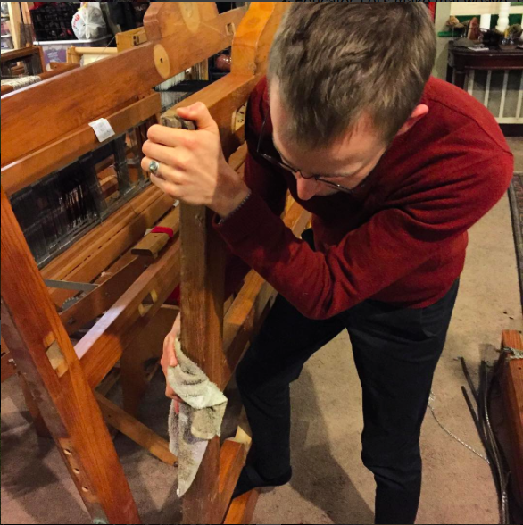 Andrew Carter diligently cleans the frame of a cranbrook loom