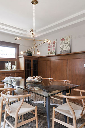 This whimsical polished brasspendant shines next to the dark,powder coated steeltable legs, and the polished nickelused in the kitchen contrasts with the dining room and sets the space at a less formal tone.