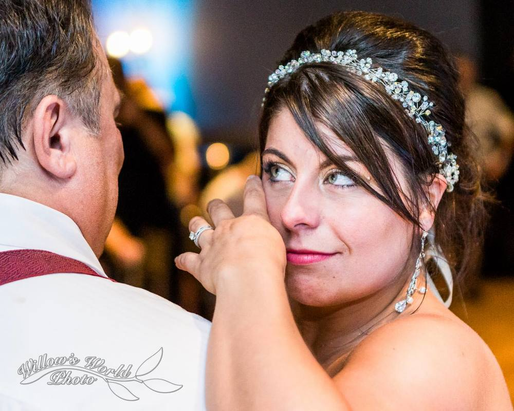 The bride wipes a few happy tears as she dances with her father...