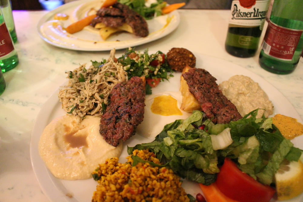 The Mixed Dish from Yarok in Berlin, Germany.  Falafel, haloumi, zucchini fritters, Makaly, Huomus, Tabula, couscous, and mutabel