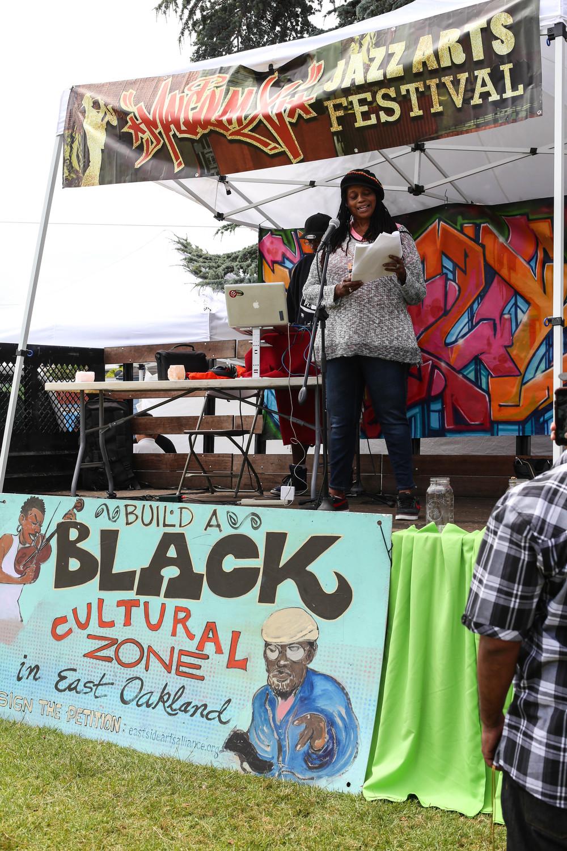 Ayodele Nzinga, The WordSlanger, of Oakalnd, reads a poem on at the event.