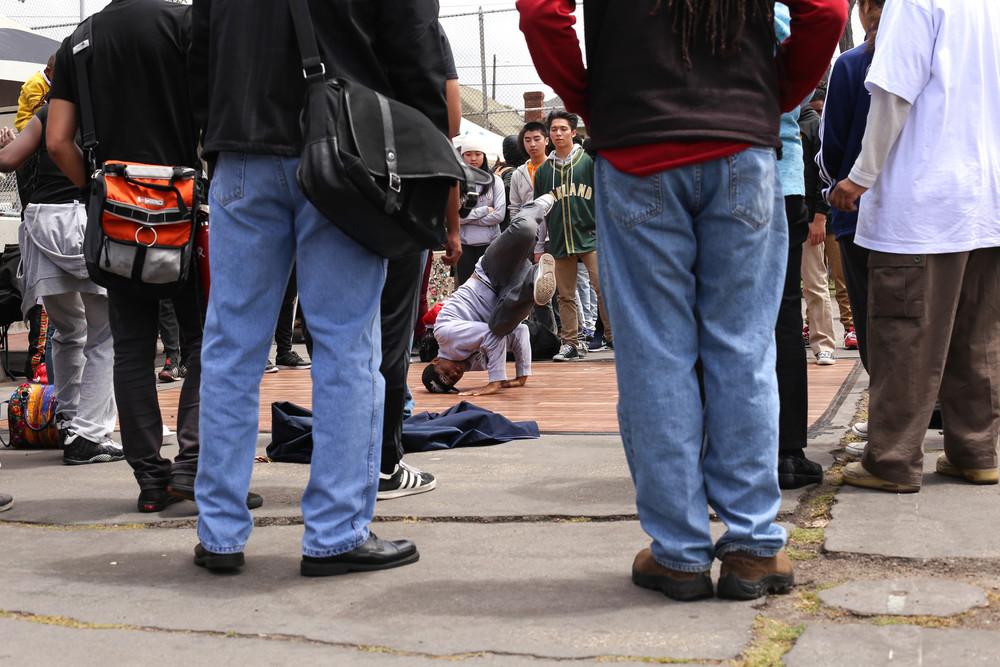 A crowd forms around a breakdancer.