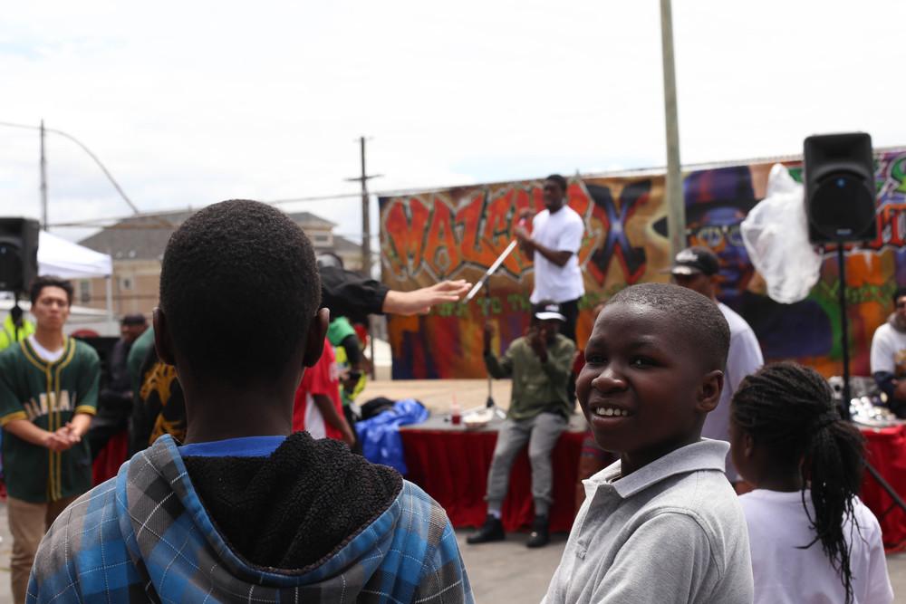 Syliss (age 12), Nehemiah (age 10) & Asokahfaye (age 7) of Oakland enjoy watching the breakdancers preform.